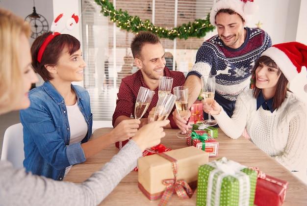 Glückliches team, das an der weihnachtsbüroparty anstößt