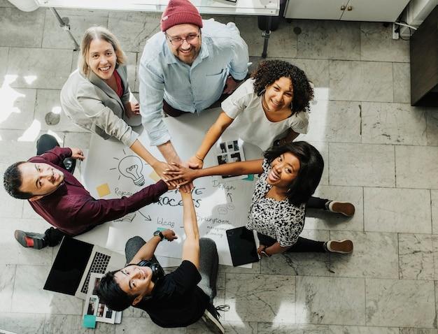 Glückliches team, das hände an einem kreativen ideendiagramm stapelt
