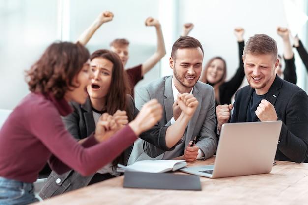 Glückliches team von mitarbeitern, die auf den laptop-bildschirm schauen