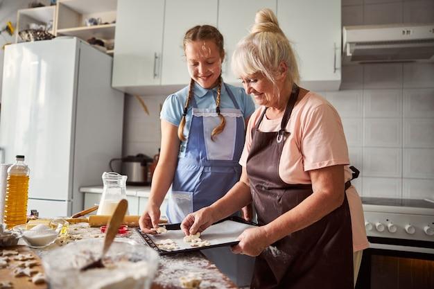 Glückliches teenager-mädchen, das ihrer oma in der küche hilft