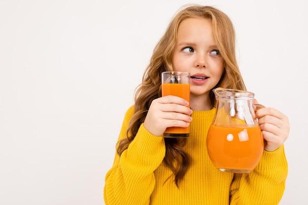 Glückliches teenager-mädchen mit roten haaren, kapuzenpulli und gelber hose trinkt karottensaft isoliert auf weiß