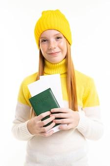 Glückliches teenager-mädchen mit roten haaren, kapuzenpulli und hut hält einen pass und tickets lokalisiert auf weißem hintergrund