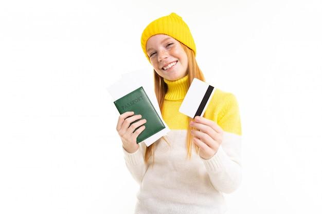 Glückliches teenager-mädchen mit roten haaren, kapuzenpulli und hut hält pass und kreditkarte lokalisiert auf weißem hintergrund
