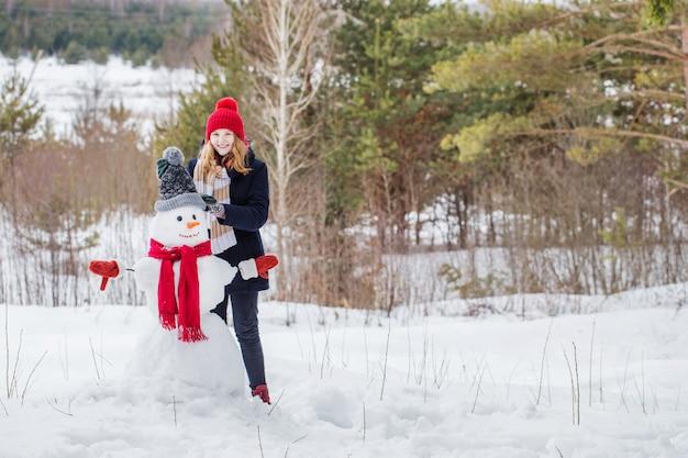 Glückliches teenager-mädchen mit schneemann im winterwald