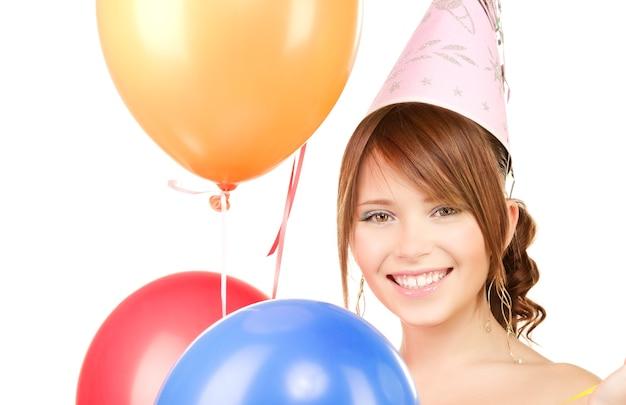 Glückliches teenager-partygirl mit luftballons über weiß