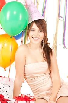 Glückliches teenager-partymädchen mit ballons und geschenkbox