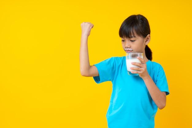 Glückliches thailändisches kind, das glas milch, trinkmilch des jungen asiatischen mädchens für starke gesundheit lokalisiert hält