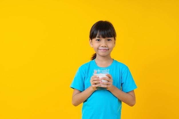 Glückliches thailändisches kind, das glas milch, trinkmilch des jungen asiatischen mädchens lokalisiert hält