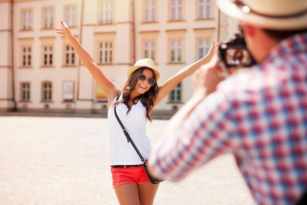 Glückliches touristenmädchen, das für foto aufwirft