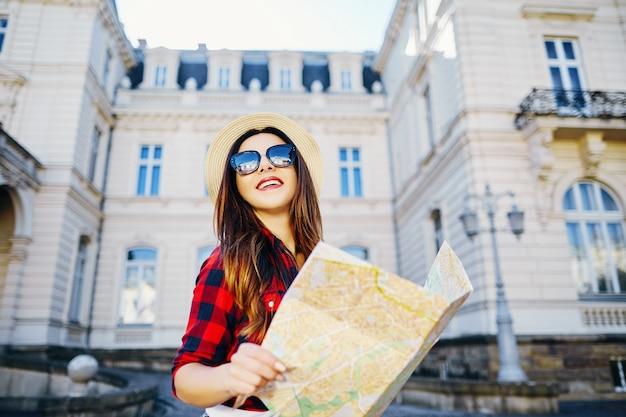 Glückliches touristenmädchen mit braunem haar, das hut und rotes hemd trägt, karte am alten europäischen stadthintergrund hält und lächelt, reist, porträt.