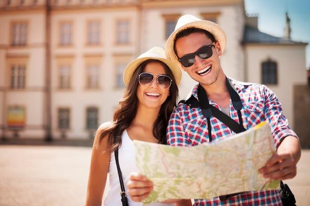 Glückliches touristenpaar, das karte hält