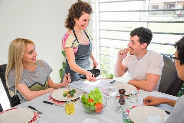 Glückliches umhüllungslebensmittel der jungen frau zu ihrem freund, der auf tabelle sitzt