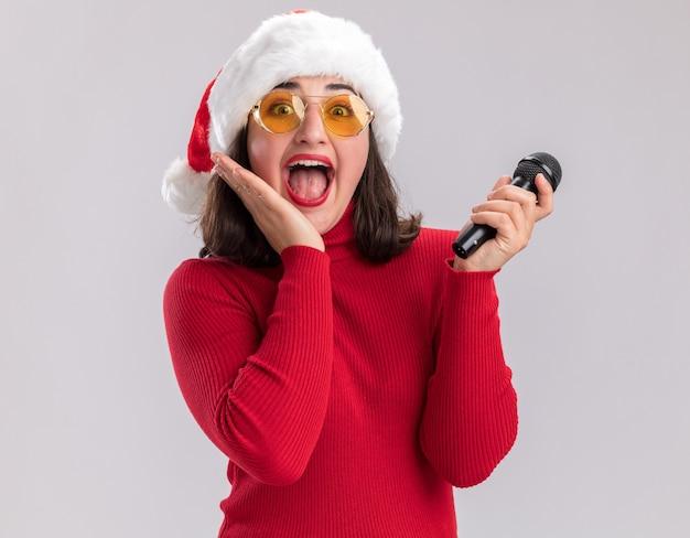 Glückliches und aufgeregtes junges mädchen im roten pullover und in der weihnachtsmannmütze, die die brille hält, die das mikrofon hält, das kamera betrachtet, die über weißem hintergrund steht