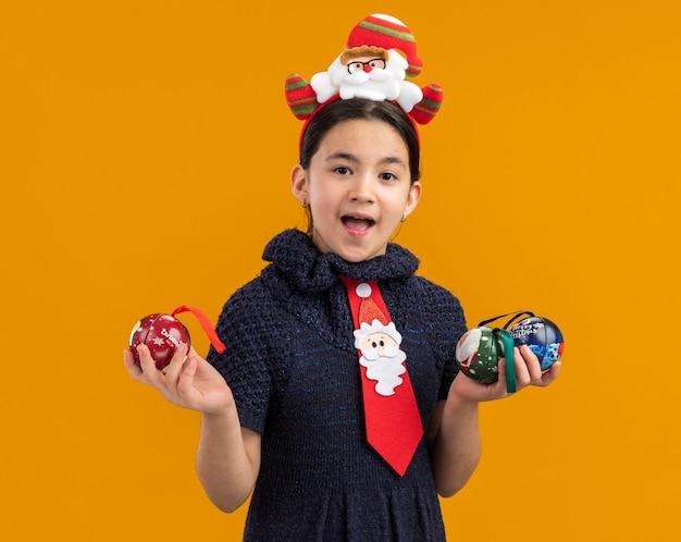 Glückliches und aufgeregtes kleines mädchen im strickkleid, das rote krawatte mit lustigem rand auf kopf hält, der weihnachtskugeln hält und fröhlich lächelt
