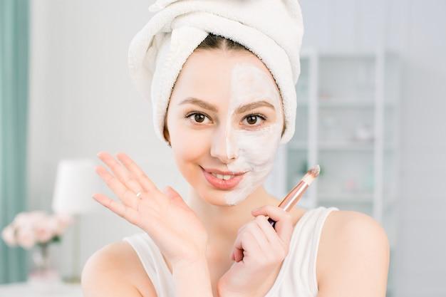 Glückliches und emotionales spa-mädchen, das gesichtsmaske anwendet. ästhetisches verfahren. das mädchen trägt mit einem pinsel eine anti-aging-maske aus ton auf die hälfte des gesichts auf