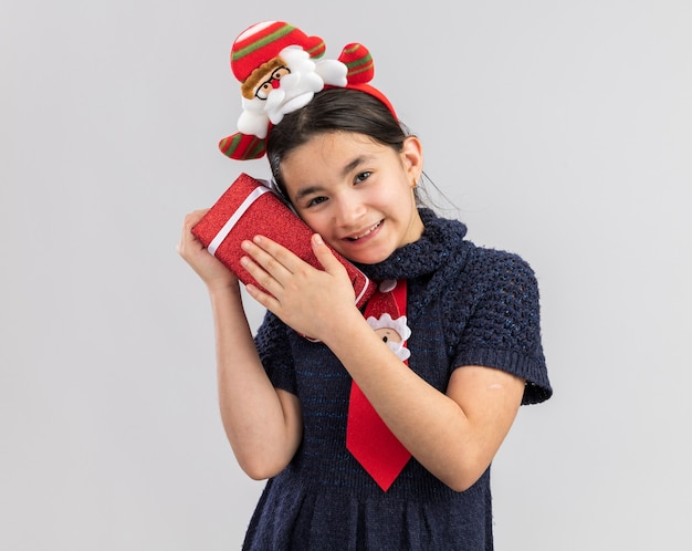 Glückliches und erfreutes kleines mädchen im strickkleid, das rote krawatte mit lustigem weihnachtsrand auf kopf hält, der weihnachtendes weihnachtsgeschenk hält