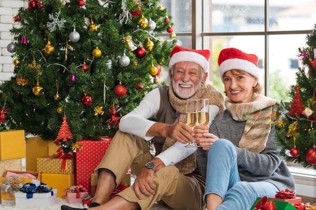 Glückliches und fröhliches kaukasisches seniorenpaar, das zusammen champagnerflöte hält und anfeuert, um weihnachten mit geschmücktem weihnachtsbaum und geschenken zu hause zu feiern. weihnachts- und neujahrsfestaktivität.