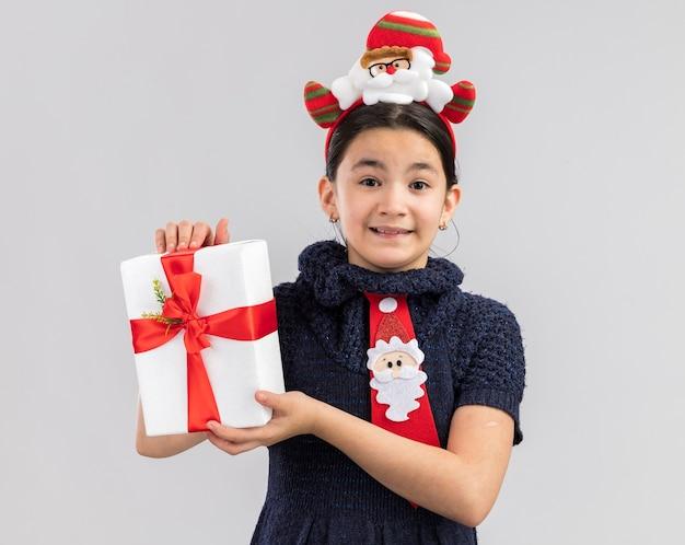 Glückliches und fröhliches kleines mädchen im strickkleid, das rote krawatte mit lustigem weihnachtsrand auf kopf hält, der weihnachtsgeschenk hält, das mit lächeln auf gesicht schaut