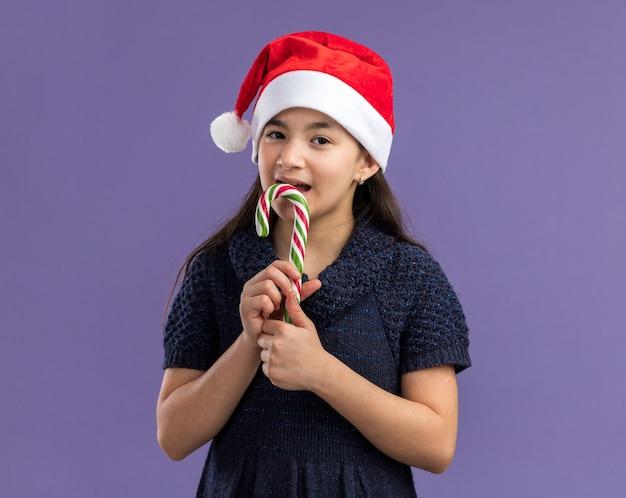 Glückliches und fröhliches kleines mädchen im strickkleid, das weihnachtsmütze hält, die zuckerstange hält, die mit lächeln auf gesicht schaut, das zuckerrohr beißt