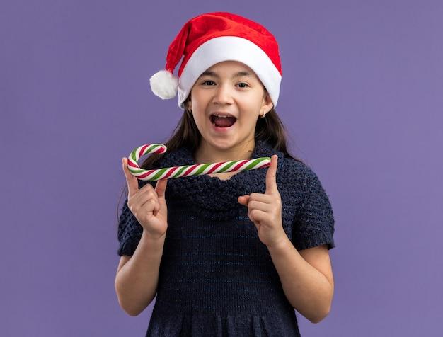 Glückliches und fröhliches kleines mädchen im strickkleid, das weihnachtsmütze hält, die zuckerstange hält, die mit lächeln auf gesicht schaut