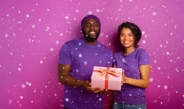 Glückliches und fröhliches paar zeigen ihr weihnachtsgeschenk