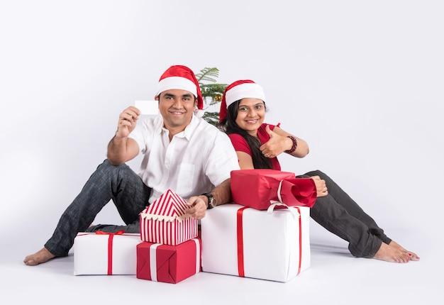 Glückliches und junges indisches paar mit weihnachtsgeschenken, auf weißem hintergrund