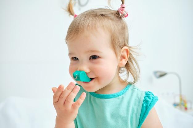 Glückliches und lächelndes kleinkind, das mit einer spielzeugpfeife spielt