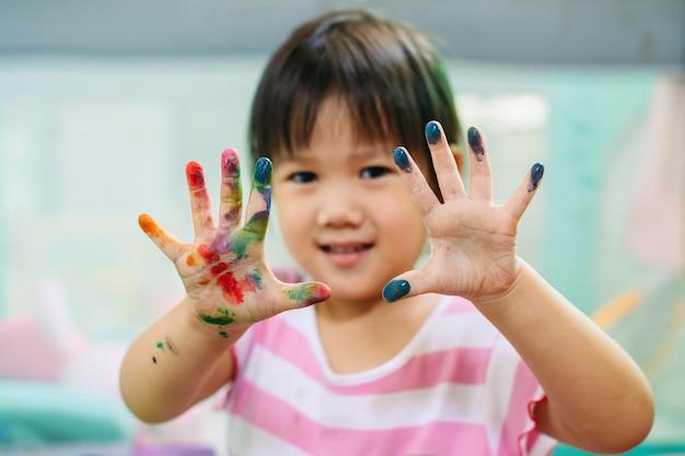 Glückliches und nettes mädchen benutzt die hände und die finger für fingermalereikunstarbeit.
