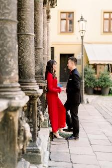 Glückliches und reizendes chinesisches paar von mann und frau, die einander in der altstadt schauen.