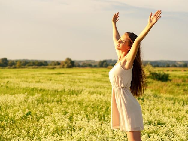Glückliches und ruhiges verhalten frau im freien mit erhobenen händen junges fröhliches mädchen ist auf der natur über dem frühlingsfeld glücksmenschen hübsches und freudiges modell entspannt sich auf der wiese