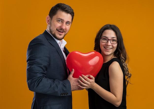 Glückliches und schönes paar, mann und frau mit rotem ballon in herzform, die den valentinstag über orangefarbener wand umarmen?