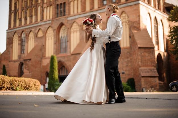 Glückliches und schönes verheiratetes paar, das im hintergrund des vintagen roten backsteingebäudes am sonnigen tag tanzt