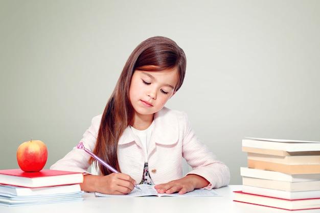 Glückliches und süßes teenager-schulmädchen schreibt in ein buch oder ein notizbuch