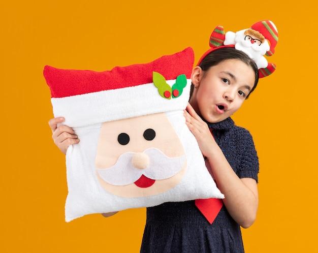 Glückliches und überraschtes kleines mädchen im strickkleid, das rote krawatte mit lustigem rand auf kopf hält, der weihnachtskissen hält, das fröhlich lächelnd schaut
