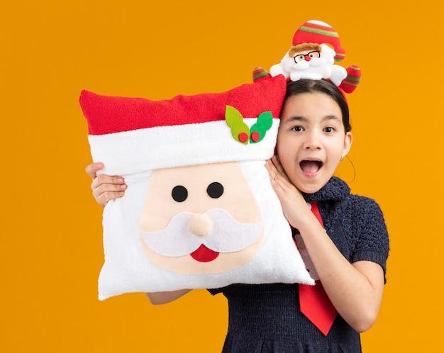 Glückliches und überraschtes kleines mädchen im strickkleid, das rote krawatte mit lustigem rand auf kopf hält, der weihnachtskissen hält und fröhlich lächelt