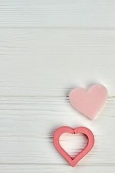 Glückliches valentinstagkonzept auf hölzernem hintergrund. zwei rosa herzen auf hellem holz mit kopienraum. liebes- und romantikkonzept.