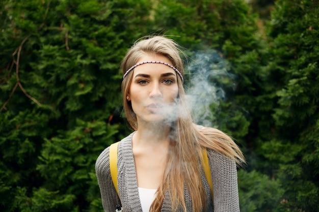 Glückliches vaping junges weißes blondes mädchen. lächelndes weibliches modell, das e-liquid oder e-saft mit fruchtgeschmack raucht, mit verdampfergerät oder e-zigarette