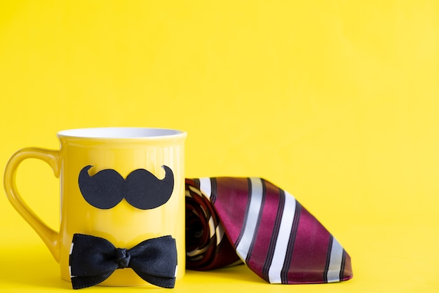Glückliches vatertagskonzept auf gelber pastellkaffeetasse auf gelbem hintergrund.