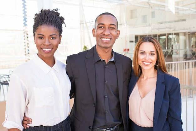 Glückliches vereinigtes multiethnisches team, das in der bürohalle aufwirft