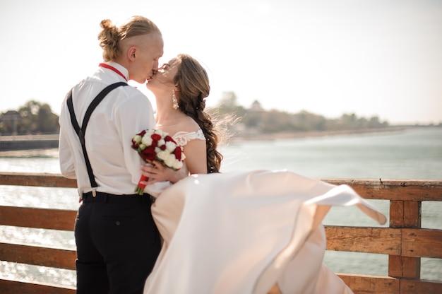 Glückliches verheiratetes paar, das auf der hölzernen brücke im hintergrund des meeres und des himmels küsst