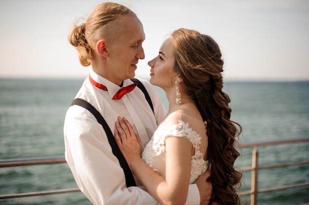 Glückliches verheiratetes paar, das im hintergrund des meeres und des horizonts des blauen himmels am sonnigen tag umarmt