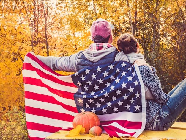 Glückliches verheiratetes paar, welches die us-flagge hält