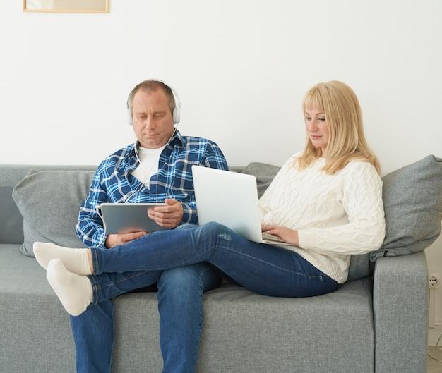 Glückliches verheiratetes paar zu hause, das auf elektronischen geräten sucht