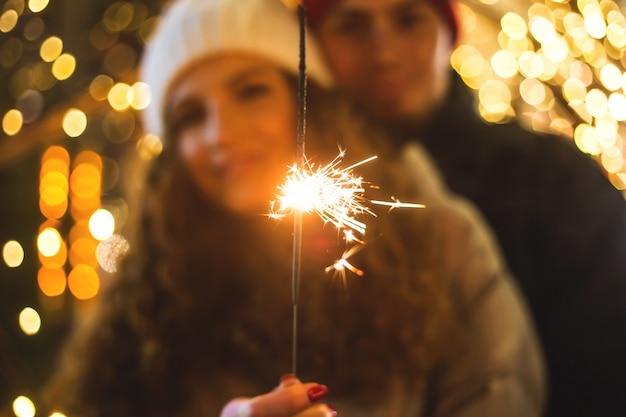 Glückliches verliebtes paar in einer weihnachtsatmosphäre mit wunderkerze.