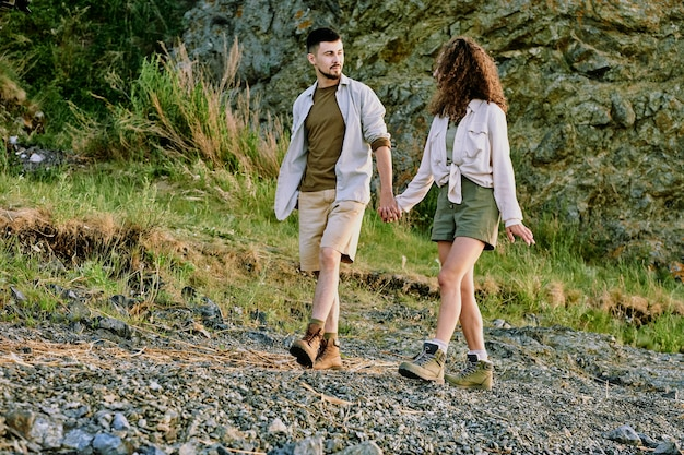 Glückliches verliebtes paar in freizeitkleidung, das einander ansieht und etwas bespricht, während es an den händen hält und sich das flussufer hinunterbewegt