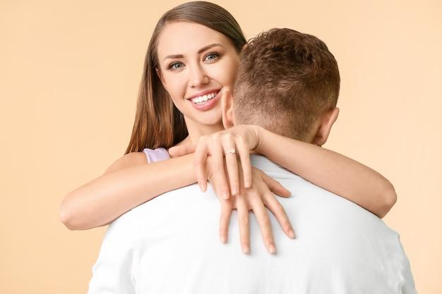 Glückliches verlobtes junges paar auf farbe