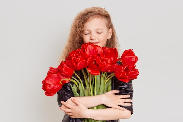 Glückliches verträumtes kleines blondes mädchen, das viele rote tulpen umarmt und augen geschlossen hält, schönes geschenk genießt, schwarze jacke tragend