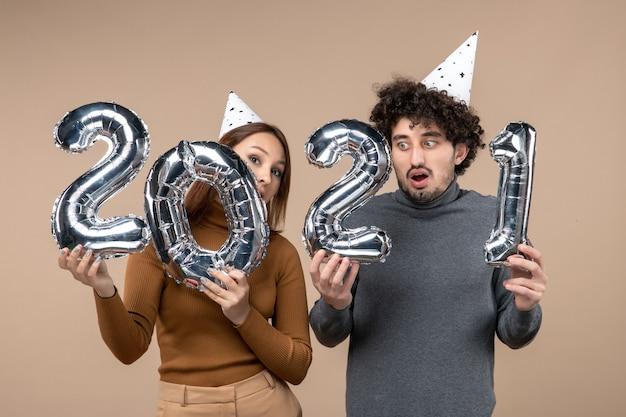 Glückliches verwirrtes junges paar tragen neujahrshut posiert für kamera mädchen zeigt und und kerl mit und auf grau