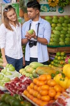 Glückliches vielfältiges junges paar, das frische früchte im lokalen supermarkt wählt
