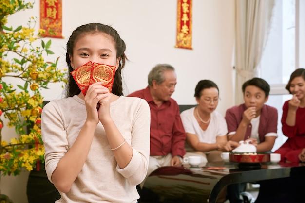 Glückliches vietnamesisches mädchen, das umschläge mit hält